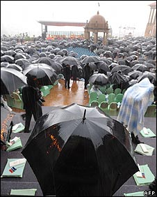 Guests take cover from the rain under umbrellas at the Union Buildings in Pretoria on 9/5/09