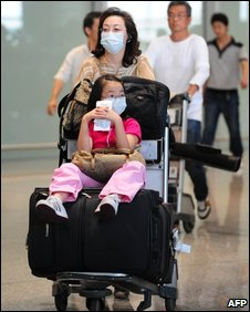 Travellers arrive wearing protective facemasks at Beijing airport on May 7, 2009