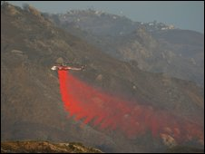 A firefighting helicopter drops Phos-Chek fire retardant at the Jesusita fire on 10 May, 2009 in Santa Barbara, California