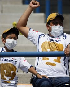 Fans wearing face masks watch a football game in Mexico City on 10 May