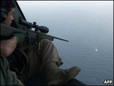South Korean military sniper on a helicopter aiming at a pirate boat off Somalia