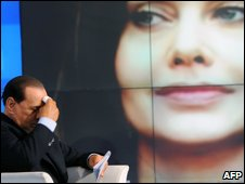 Berlusconi is seen while a portrait of his wife Veronica