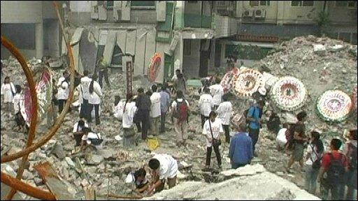 People gathered around destroyed school building in Beichuan