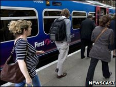 Passengers walk past a First Capital Connect train