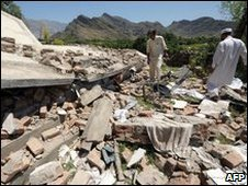Residents inspect the rubble of a police post in Malakand district, 13 May