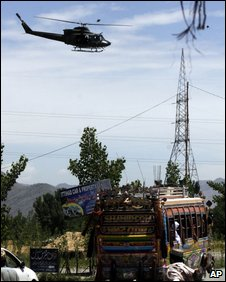 A Pakistani army helicopter flies as residents of Chakdara in Lower Dir flee fighting