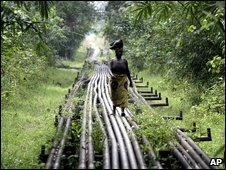 woman walks along an oil pipeline near Shell's Utorogu flow station in Warri, Nigeria
