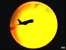 A plane flies in front of the sun