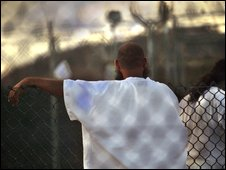 A detainee rests his arm on a fence as another passes, as dusk falls at the US Guantanamo Bay naval base detention facility
