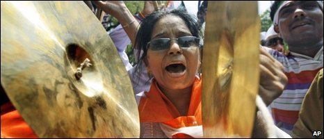 A Congress supporter crashes cymbals in celebration