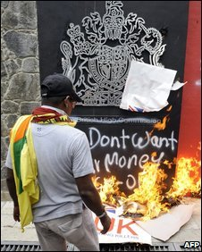 A Sri Lankan demonstrator looks on as placards burn outside the British High Commission in Colombo on May 18, 2009.