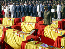 Spain's King Juan Carlos stands near the coffins of some of the victims at their state funeral (28 May 2003)