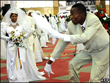 A groom dances as brides walk down the aisle at a mass wedding in South Africa