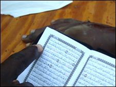 Mohamed Omar Ismail's severed hand lies on the table in the background; Koran is read in the foreground