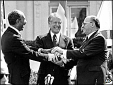 Egyptian President Anwar Sadat, left, U.S. President Jimmy Carter, center, and Israeli Prime Minister Menachem Begin clasp hands on the north lawn of the White House