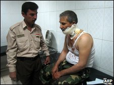 A colleague looks after an injured officer at a hospital in Kirkuk