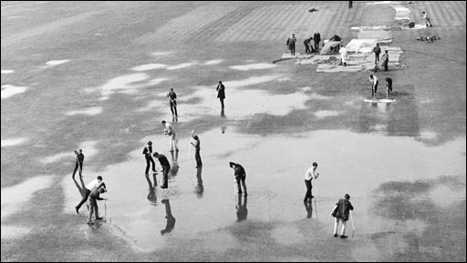 Volunteers attempt to mop up a wet Oval pitch during the fifth Test