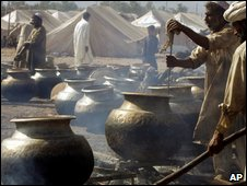 Cooks prepare food at a refugee camp