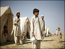 Refugees wait for food to be delivered to their tents at a refugee camp in Sangjani, outside Islamabad,