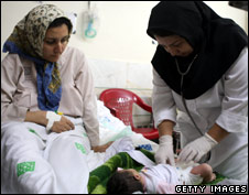 Mother and nurse tend to a baby in hospital