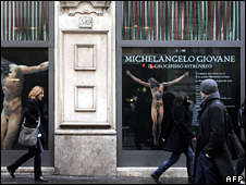 Italians walk past a poster advertising an exhibition including the statue (2 January 2009)