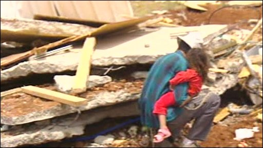 Man and child at the destroyed settlement