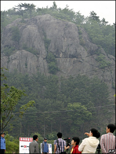 Police, wearing blue jackets, stand guard in front of the Bonghwa mountain, where Roh Moo-hyun is believed to have died (23 May 2009)