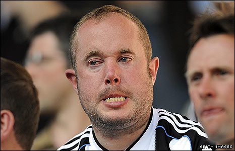 A Newcastle fan struggles to hold back the tears at Villa Park
