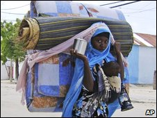 A woman flees the fighting in Mogadishu on Sunday 24 May