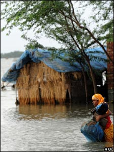 A woman walks through the flooded village of Minakhan, 50 km south-east of Kolkata on May 26, 2009.