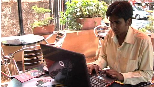 Man using laptop in Mumbai internet cafe
