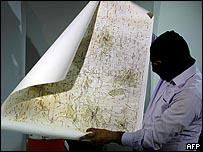 رجل أمن لبناني يمسك بخريطة ضبطت لدى أحد المعتقلين