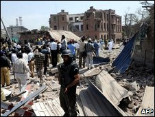 Pakistani security officials and volunteers gather in front of the destroyed police emergency response office building  - May 27