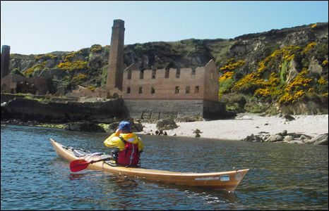 Mike Bell paddles the wooden kayak he designed and built himself by the old brick works at Porth Wen, Anglesey (Ian Collins).