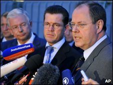 From right, German Finance Minister Peer Steinbrueck, German Economic Minister Karl-Theodor zu Guttenberg, and Roland Koch, prime minister of German Sstate Hesse, talk during a news conference in front of the Chancellery in Berlin