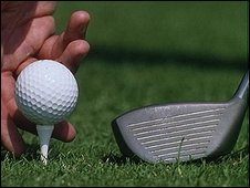 Golf club, ball and tee and a hand