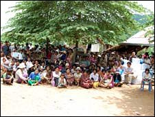Dozens of villagers sitting under a large tree, waiting for mosquito nets to be distributed.