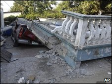 Stone balcony which has fallen on top of a car.