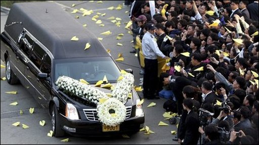 The hearse, surrounded by supporters and yellow paper planes