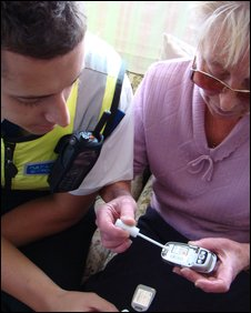 Officer shows a resident how to use the SmartWater
