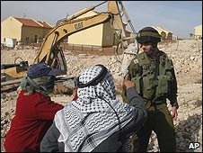 Palestinians confront an Israeli soldier at a protest against the expansion of the Carmel settlement in the West Bank town of Hebron (26 April 2009)