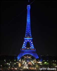 The Eiffel Tower is illuminated in blue with gold stars, representing the EU flag