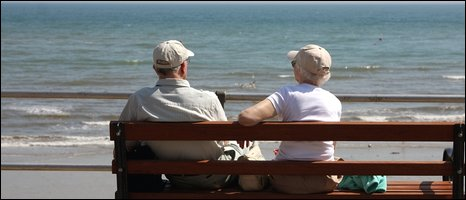 Two older people sitting on a bench watching the sea