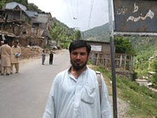 Sher Mohammad. The road sign beside him says Matta Aghwan, the name of the town