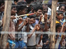 People in Sri Lanka wait behind barbed wire during a visit by UN Secretary-General Ban Ki-moon at Manik Farm refugee camp on May 23, 2009