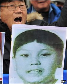 South Korean protester shouts slogans while holding a picture of a boy believed to be the third son of North Korean leader Kim Jong-il, Kim Yong-un, February 19, 2009