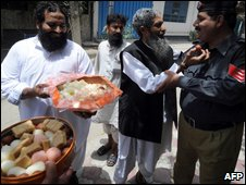 A supporter of the banned Islamic party Jamaat-ud-Dawa (JuD) offers sweets to a policeman after the court ruling in Lahore