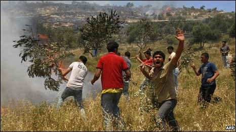 A Palestinian man yells in anger as his companions try to put out fires in fields set by Israeli settlers in the West Bank.