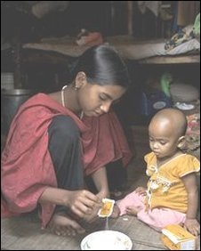 Bangladeshi girl feeds a younger child