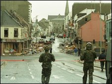 Soldiers look on at the scene of the Omagh bomb from behind a police cordon
